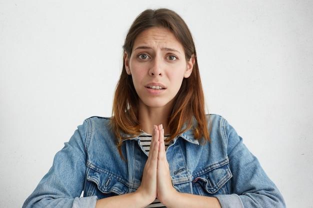 Jovem mulher com jaqueta jeans pedindo perdão