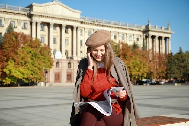 Jovem mulher com jornal ao ar livre