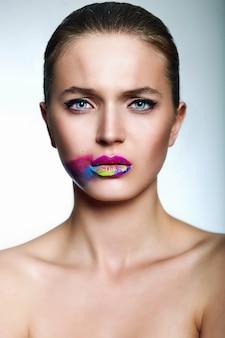 Jovem mulher com lábios brilhantes coloridos criativos