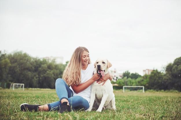 Jovem mulher com labrador ao ar livre. mulher em uma grama verde com cachorro labrador retriever.