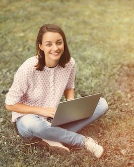 Jovem mulher com laptop sentado na grama verde