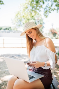 Jovem mulher com laptop usando telefone celular, sentada no banco do parque de verão da cidade