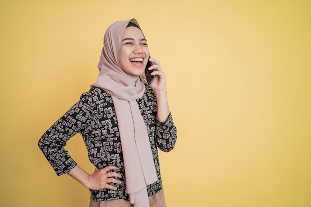 Jovem mulher com lenço na cabeça, sorrindo amplamente e relaxando as mãos na cintura ao receber uma ligação com feliz.