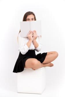 Jovem mulher com livro sobre fundo branco