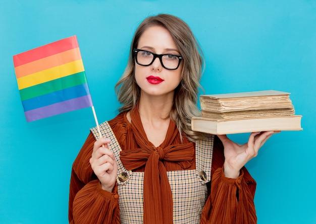 Jovem mulher com livros e bandeira lgbt no fundo azul