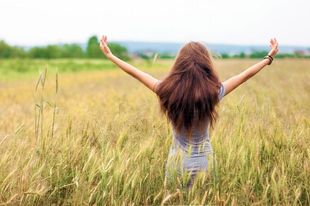 Jovem mulher com longos cabelos castanhos em pé no campo de trigo