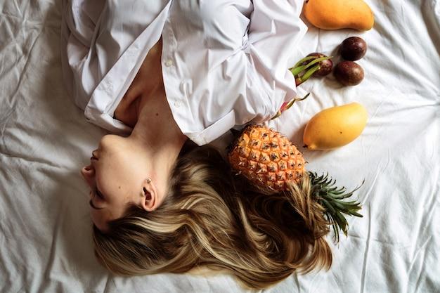 Jovem mulher com longos cabelos loiros, deitada na cama