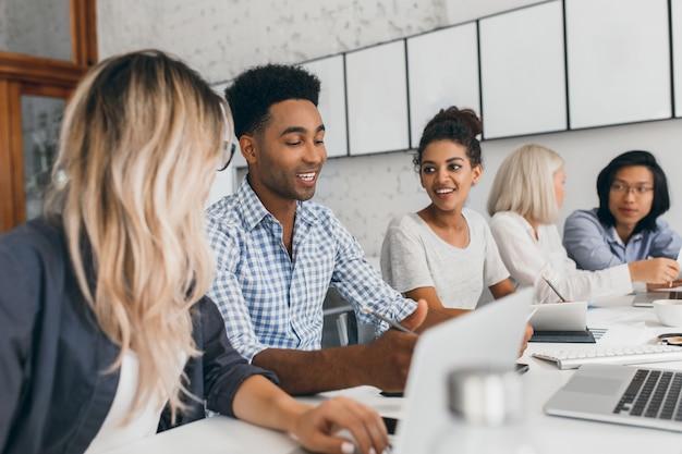 Jovem mulher com longos cabelos loiros ouvindo homem africano de camisa azul que usando o laptop. retrato interno de trabalhadores de escritório negros e asiáticos conversando durante a conferência.