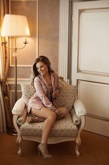 Jovem mulher com longos cabelos loiros platinados em pijama rosa de cetim no interior clássico.