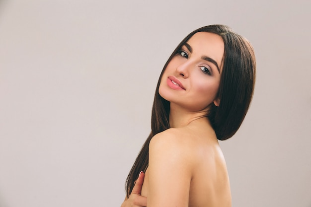 Jovem mulher com longos cabelos negros posando. morena olha em linha reta e sorri. corpo nu.
