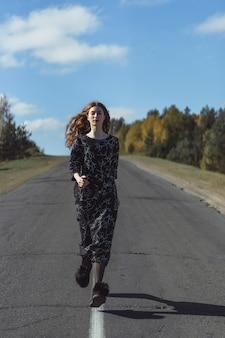 Jovem mulher com longos cabelos ruivos em um vestido de linho em um local natural no fundo