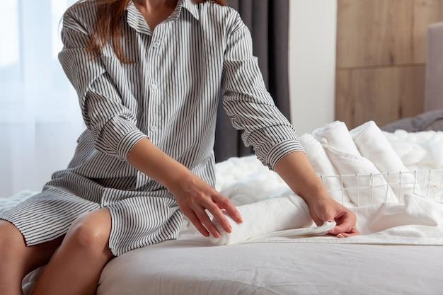 Jovem mulher com longos cabelos vermelhos está sentada na cama e dobrando toalhas de mão brancas e limpas em uma cesta de malha no quarto. pilha de enrolar toalhas com espaço de cópia. linho limpo e arrumado. têxtil hipoalergênico.