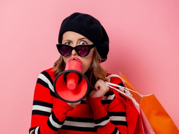 Jovem mulher com luoder e sacos de compras na parede rosa