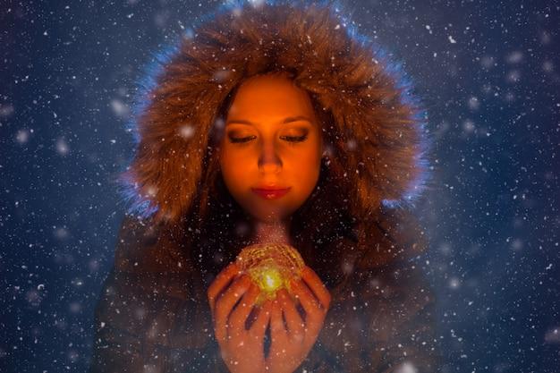 Jovem mulher com luz mágica nas mãos à noite durante uma tempestade de neve