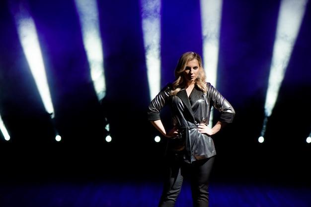 Jovem mulher com luzes coloridas em concerto no palco