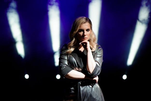 Jovem mulher com luzes coloridas em show no palco.