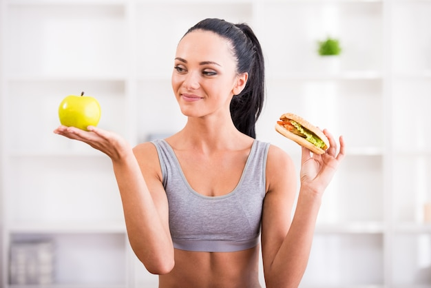 Jovem mulher com maçã e cachorro-quente após o exercício em casa.