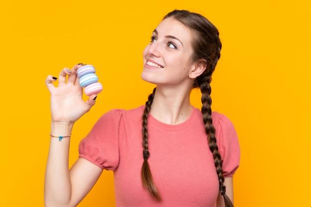 Jovem mulher com macarons sobre parede isolada