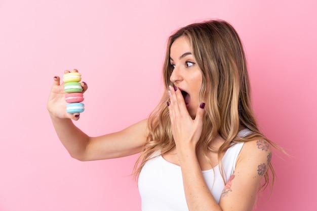 Jovem mulher com macarons sobre parede rosa isolada com surpresa e expressão facial chocada