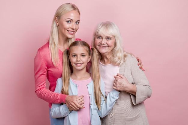 Jovem mulher com mãe e avó e de mãos dadas