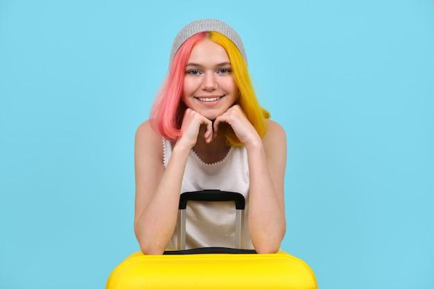 Jovem mulher com mala amarela, sorridente menina adolescente hippie com cabelos tingidos de cor, olhando para a câmera. fundo azul do estúdio. turismo, viagens, estilo de vida, estudantes, conceito em movimento