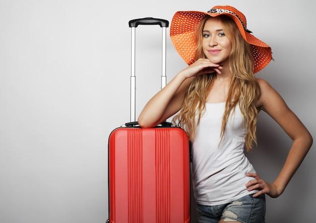 Jovem mulher com mala de viagem laranja