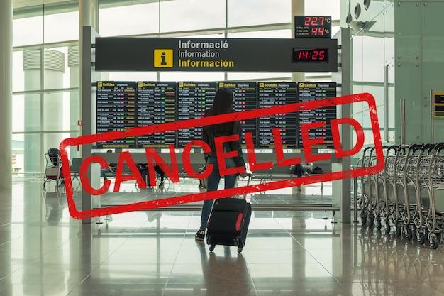 Jovem mulher com mala na sala de embarque no aeroporto.