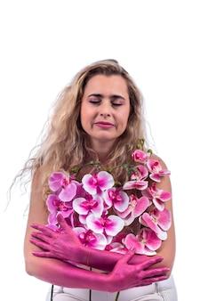 Jovem mulher com mãos-de-rosa e flores sobre um branco.