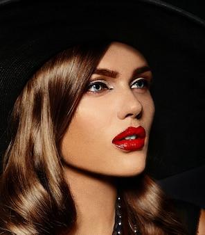 Jovem mulher com maquiagem brilhante e chapéu preto