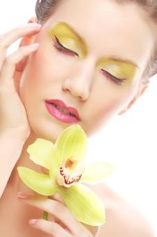 Jovem mulher com maquiagem brilhante segurando a orquídea