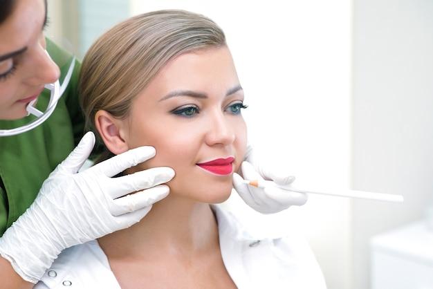 Jovem mulher com maquiagem definitiva nos lábios no salão de esteticistas. fundo verde natural