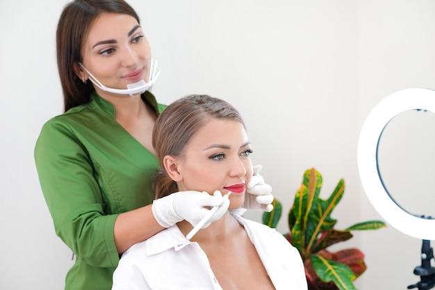 Jovem mulher com maquiagem definitiva nos lábios no salão de esteticistas.