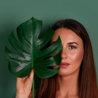 Jovem mulher com maquiagem natural e folha de monstera tropical na mão sobre fundo verde, com espaço de cópia