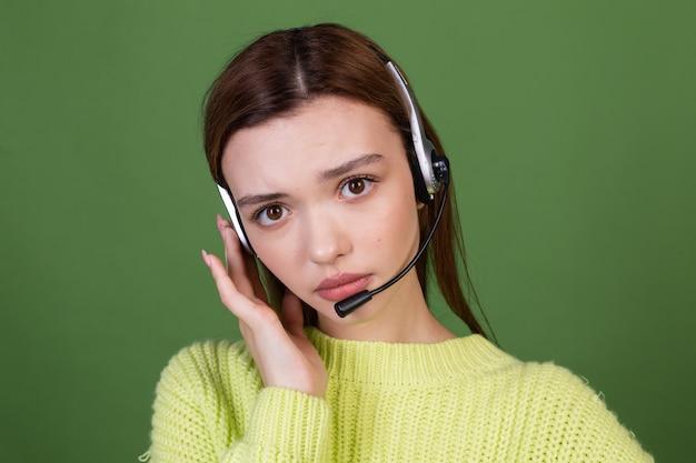 Jovem mulher com maquiagem natural perfeita, lábios grandes castanhos em suéter casual na parede verde em fones de ouvido call center trabalhador gerente cansado entediado