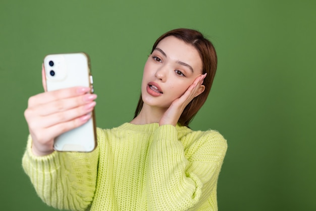 Jovem mulher com maquiagem natural perfeita, lábios grandes marrons na parede verde com celular tira uma selfie se fotografando