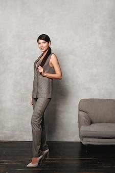 Jovem mulher com maquiagem natural, vestindo roupas de escritório formais e da moda modelo menina em moderno cinza o.