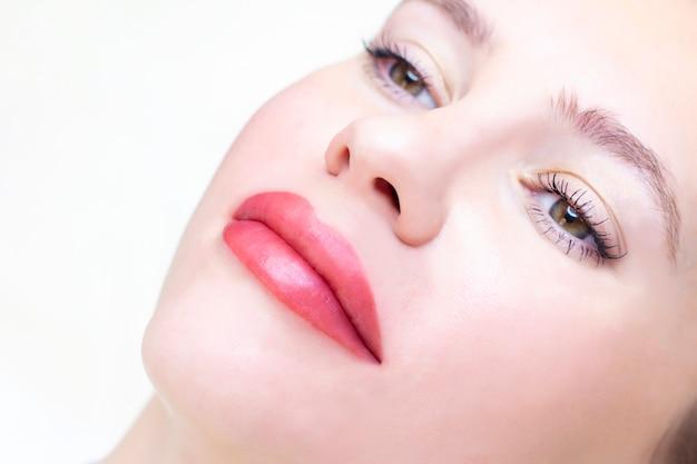 Jovem mulher com maquiagem permanente nos lábios em um salão de cosmetologistas.