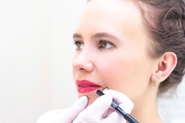 Jovem mulher com maquiagem permanente nos lábios no salão de esteticistas. maquiagem permanente (tatuagem). desenhando um contorno com um lápis labial branco