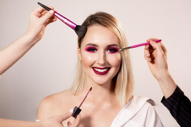 Jovem mulher com maquiagem rosa escura brilhante, posando no fundo do estúdio. as mãos do maquiador corrigem a maquiagem com um pincel especial. maquiagem profissional