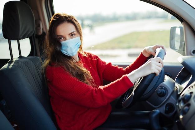 Jovem mulher com máscara de coronavírus sentado no carro