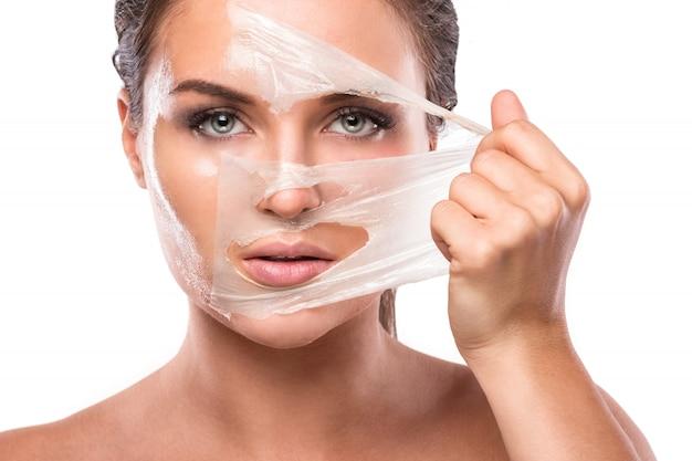 Jovem mulher com máscara de purificação no rosto