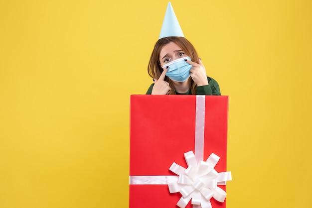 Jovem mulher com máscara dentro da caixa de presente
