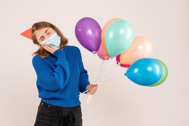 Jovem mulher com máscara estéril segurando balões coloridos de frente