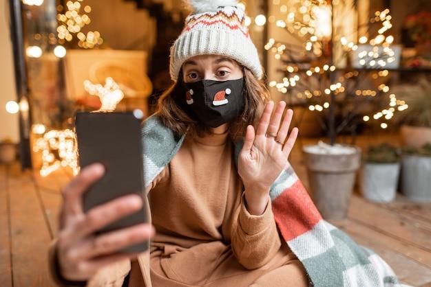 Jovem mulher com máscara facial, comemorando sozinha as férias de ano novo em casa, tendo uma videochamada no telefone. conceito de quarentena e auto-isolamento durante a epidemia nos feriados