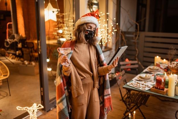 Jovem mulher com máscara facial comemorando sozinho as férias de ano novo em casa, tendo uma videochamada em um tablet. conceito de quarentena e auto-isolamento durante a epidemia nos feriados