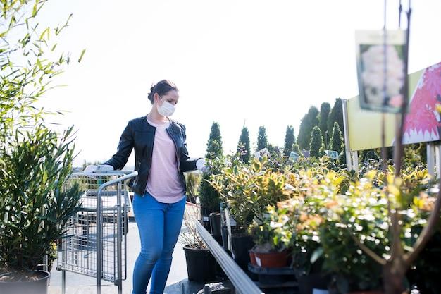 Jovem mulher com máscara facial, compras ao ar livre de plantas no centro de jardim, conceito de vírus corona.