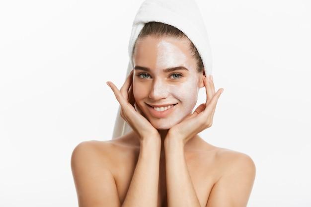 Jovem mulher com máscara facial de argila, isolada no branco.