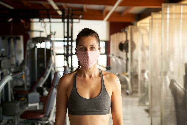 Jovem mulher com máscara facial, olhando para a câmera no ginásio.