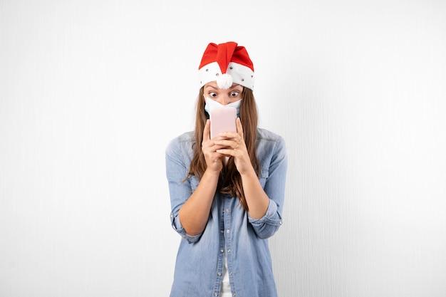 Jovem mulher com máscara médica de telefone e chapéu de papai noel. compras online de natal em quarentena.