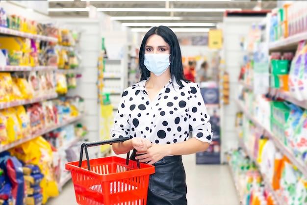 Jovem mulher com máscara médica descartável, compras no supermercado durante o surto de pneumonia por coronavírus. medidas de proteção e prevenção em tempo de epidemia.